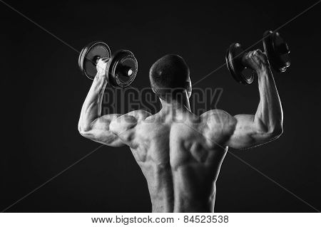 The man does sports exercises dumbbell