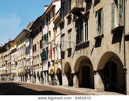 An historic road Via Vittorio Veneto in Udine in north east Italy. The line of shops and apartments is characterised by a covered walkway fronting the road. poster