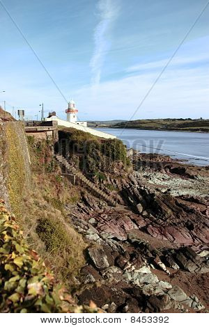 Lighthouse With Stairs Down To Rocky Beach During A Sunny Day