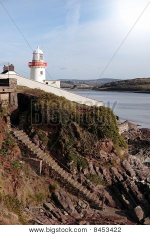 Lighthouse With Steps Down To Rocky Beach During A Sunny Day