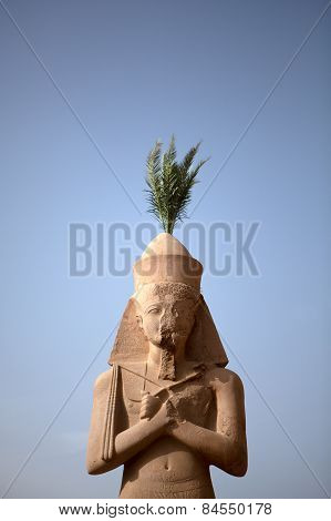 A palm tree sprouts from the top of a statues head