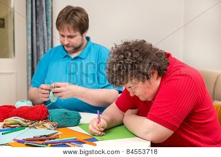 a mentally disabled woman and young man doing arts and crafts poster