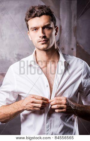 Handsome Man Buttoning Shirt.