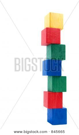 old fashioned wooden chhildren building blocks arranged  as precarious looking tower against a white background poster