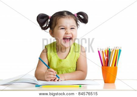 Adorable child drawing with colorful crayons and smiling