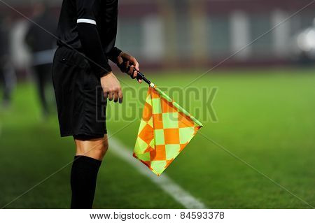Assistant referees in action during a soccer match poster
