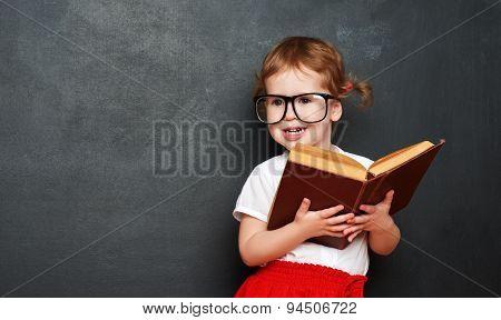 Happy  Girl Schoolgirl With Book From Blackboard