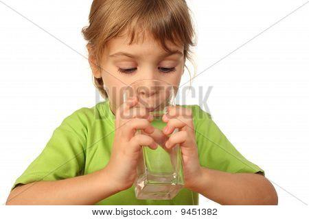 Niña con ojos cerrados beber agua del recipiente de vidrio