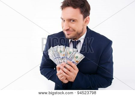 Attractive young man is keeping savings greedily