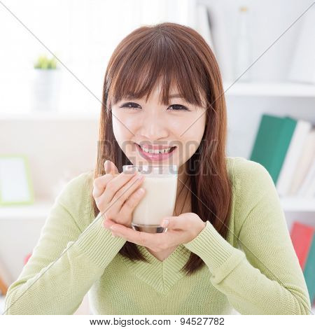 Portrait of happy Asian girl drinking soy milk as breakfast. Young woman indoors living lifestyle at home.