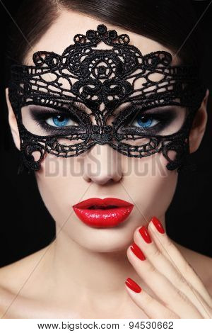 Portrait of young beautiful blue-eyed woman in black lacy mask