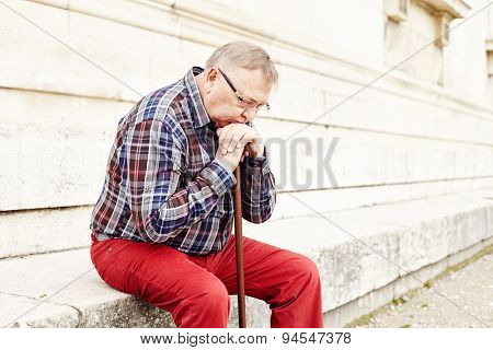 Close-up portrait of pensive mature man in glasses and plaid shirt resting leaning on his wooden walking stick