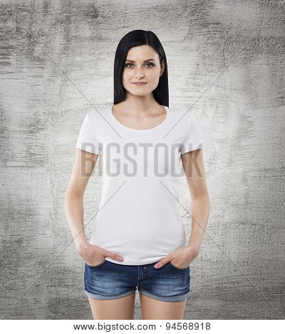 Brunette Girl In A White T-shirt And Denim Shorts. Concrete Background.