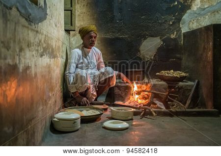 GODWAR REGION, INDIA - 12 FEBRUARY 2015: Indian man dressed in traditional clothes makes chapati on open fire in old kitchen. Chapati is an unleavened flatbread.