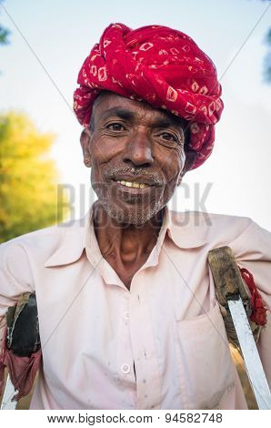 GODWAR REGION, INDIA - 12 FEBRUARY 2015: Rabari tribesman in field with crutches. Rabari or Rewari are an Indian community in the state of Gujarat.