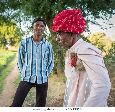 GODWAR REGION, INDIA - 12 FEBRUARY 2015: Rabari tribesman in field with crutches and son in background. Rabari or Rewari are a Indian community in the state of Gujarat.