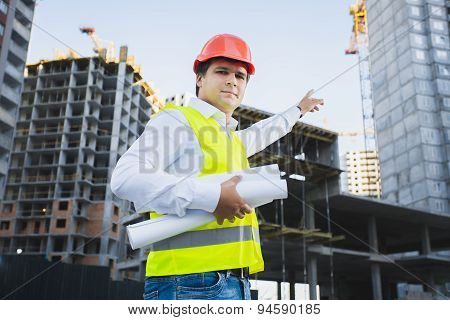Closeup Portrait Of Architect In Hardhat Showing Building