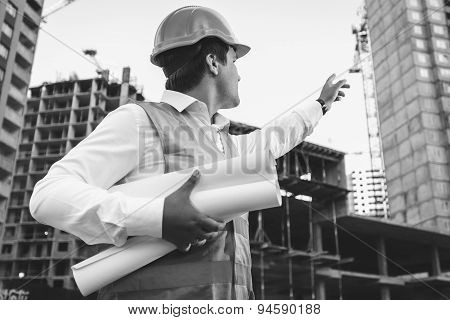 Engineer With Blueprints Checking Building Site Construction