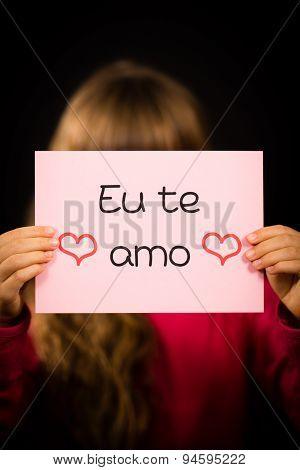 Studio shot of child holding a sign with Portuguese words Eu Te Amo - I Love You poster