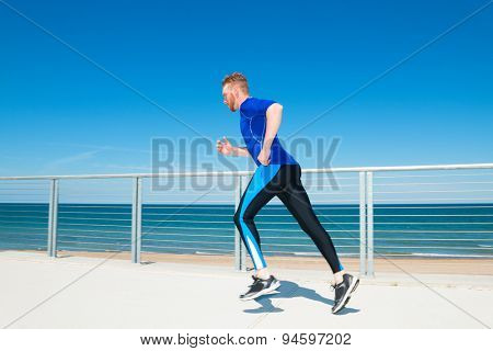 Man running or jogging at a beachside park.