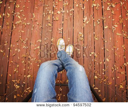 a pair of legs taken from overhead on a deck with leaves that have fallen