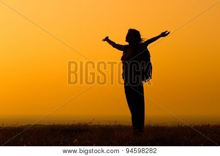 Woman hiker greeting the sunset