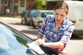 Frustrated Female Motorist Looking At Parking Ticket poster