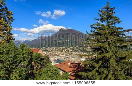 View in the city of Lugano, Switzerland, in autumn evening, mountain Monte Boglia in the background. Lugano is the largest city of the Swiss canton of Ticino.