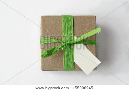 Overhead shot of a simple brown gift box with green raffia ribbon and blank label on white background.