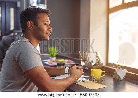 I think this is right decision. Young African guy sitting in cafe near window and making notes in notebook