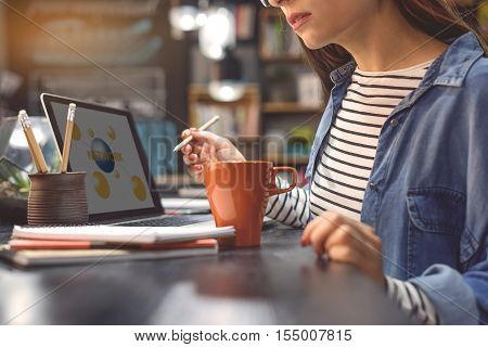 Her favorite place for coffee and wifi. Cropped shot of attractive young woman in coffee shop making notes and enjoying laptop