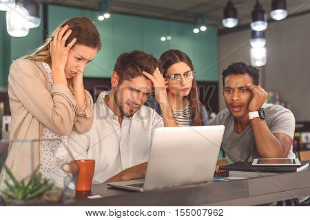 Brainstorming buddies. Photo of stressed students looking at laptop screen during sitting in cafe