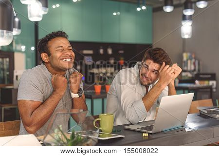 Look at this one. Happy smiling two guys enjoying while sitting in cafe and using digital gadgets