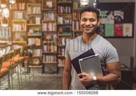 Library always has what I need. Cropped portrait of young male college student staing in library and holding digital tablet