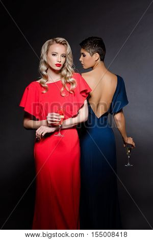 Two beautiful blonde and brunette girls in red and blue evening dresses posing, looking at camera, holding champaign glass at party over grey background. Copy space.