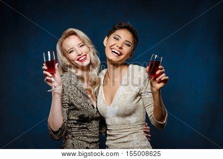 Two young beautiful blonde and brunette girls in evening dresses smiling, looking at camera, holding wine glasses at party over dark blue background. Copy space.
