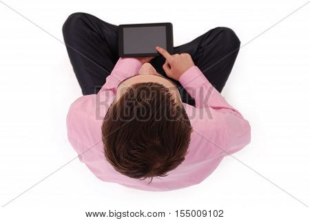 Boy in pink shirt sit and hold tablet PC isolated on white. Shallow depth