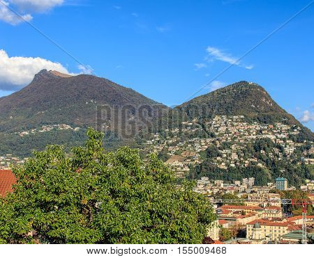 View in the Swiss city of Lugano in autumn evening, mountains Monte Boglia and Monte Bre in the background. Lugano is the largest city of the Swiss canton of Ticino.