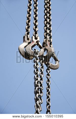 Long Chains With Hooks Hanging Vertically Against Blue Sky