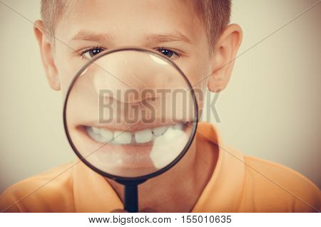 Sweet cute little boy kid showing teeth through magnifying glass.