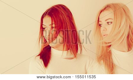 Friends dialogue between cultures. Blonde and mulatto girl together. Two young beautiful ladies one has bright hair second dark. Wearing white top.
