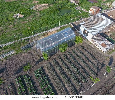 Top View Of The Garden With A Greenhouse Made Of Polycarbonate