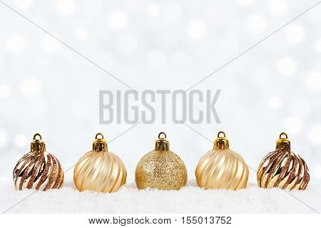 Gold Christmas Ornaments In Snow With Twinkling Silver Background