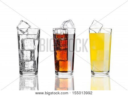 Glasses of cola orange soda lemonade with ice on white background with reflection