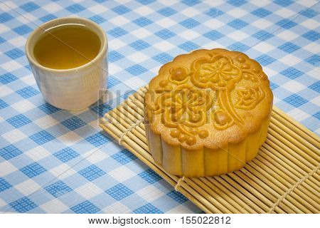 Mid-Autumn Festival moon cake on wooden broad with tea cup