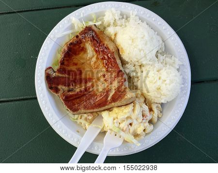 Ahi on plastic plate with mac salad two scoops of rice with plastic knife and fork.