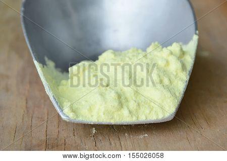 sulfur powder in iron scoop on wooden board