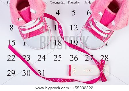 Pregnancy Test With Positive Result And Baby Shoes On Calendar, Expecting For Baby