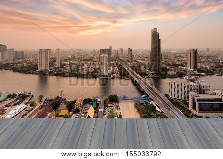 Opening wooden floor, Bangkok city river curved with dramatic sky background, Thailand