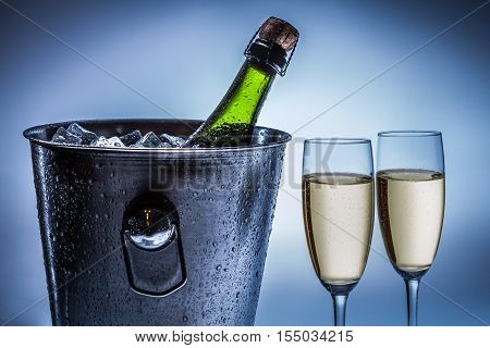 Cold chilled champagne in ice bucket on blue background